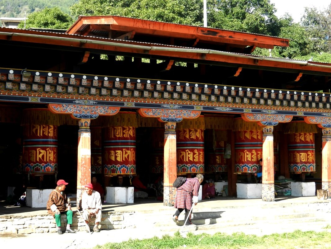 Elders spend their day spinning clunky prayer wheels