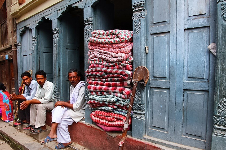 Local men chilling in a doorway, Kathmandu. The man in white attire is in mourning. When a family member passes away, you must wear white clothing for 12 months as a symbol of cleansing, purity and mourning.