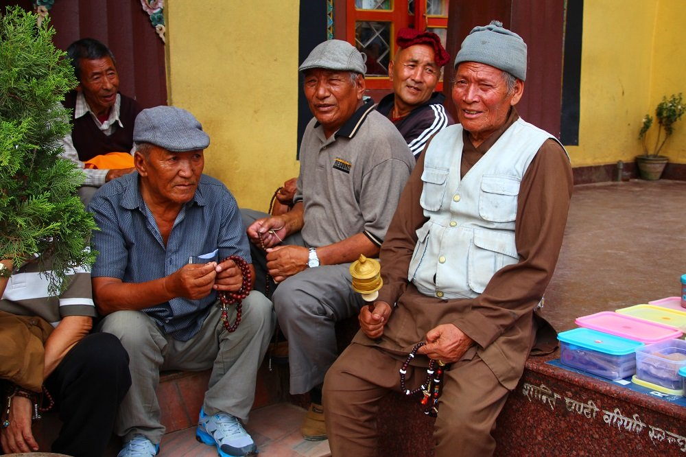 Tibetan men gather in front of a small monastery at Boudhanath Stupa, prayer wheels in hand.