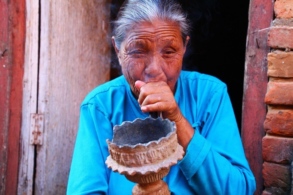 An elderly lady sits in her doorway smoking tobacco, Panauti, Kathmandu Valley.