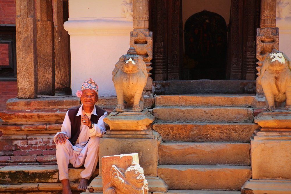 Local man in his 'topi' sitting by a small temple inside the Royal Palace, Patan, Kathmandu Valley.
