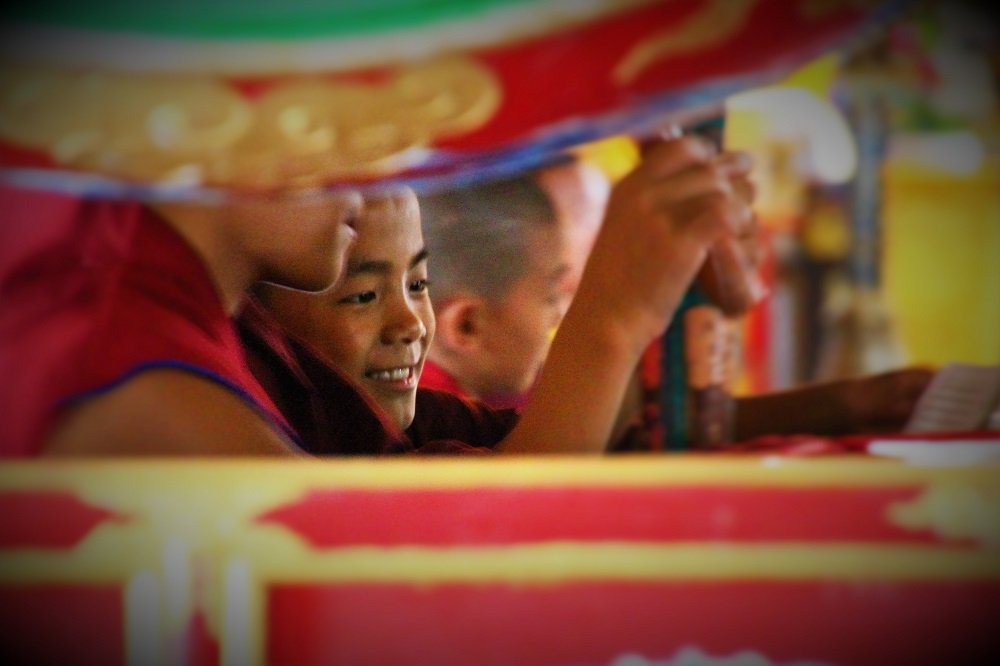 Captured this young monk grinning during the daily protection puja, with the constant beating of drums, blowing of the conch shell and long traditional horns at Neydo Tashi Choeling Monastery.