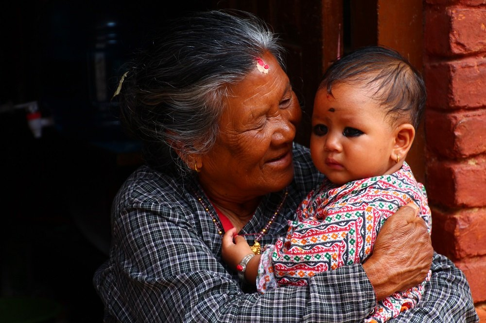 A grandmother and her grandaughter share a special moment in Changunaraya. The black charcoal under the babies eyes is to keep bad spirits away.