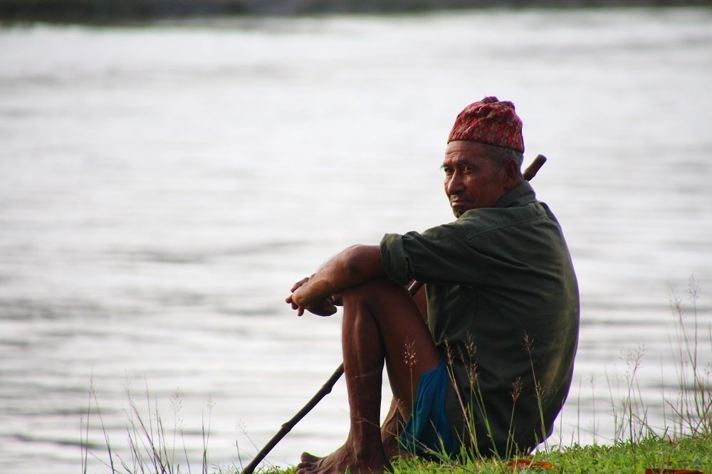 Local Tharu man sitting on the banks of the river, Chitwan National Park.