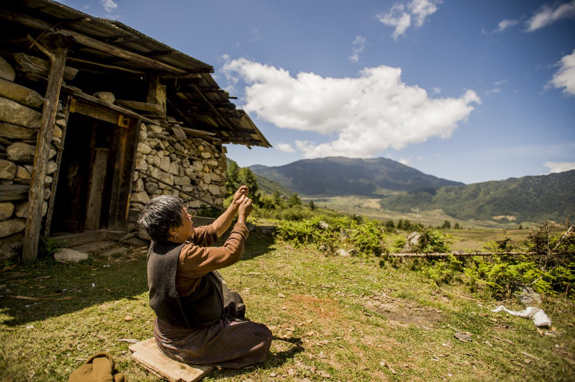 An elderly lady spins wool outside her home, Bhutan.