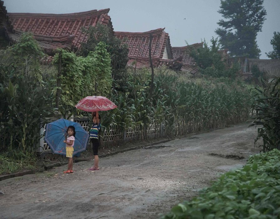 Young children seek shelter from the rain in Sinchon Village