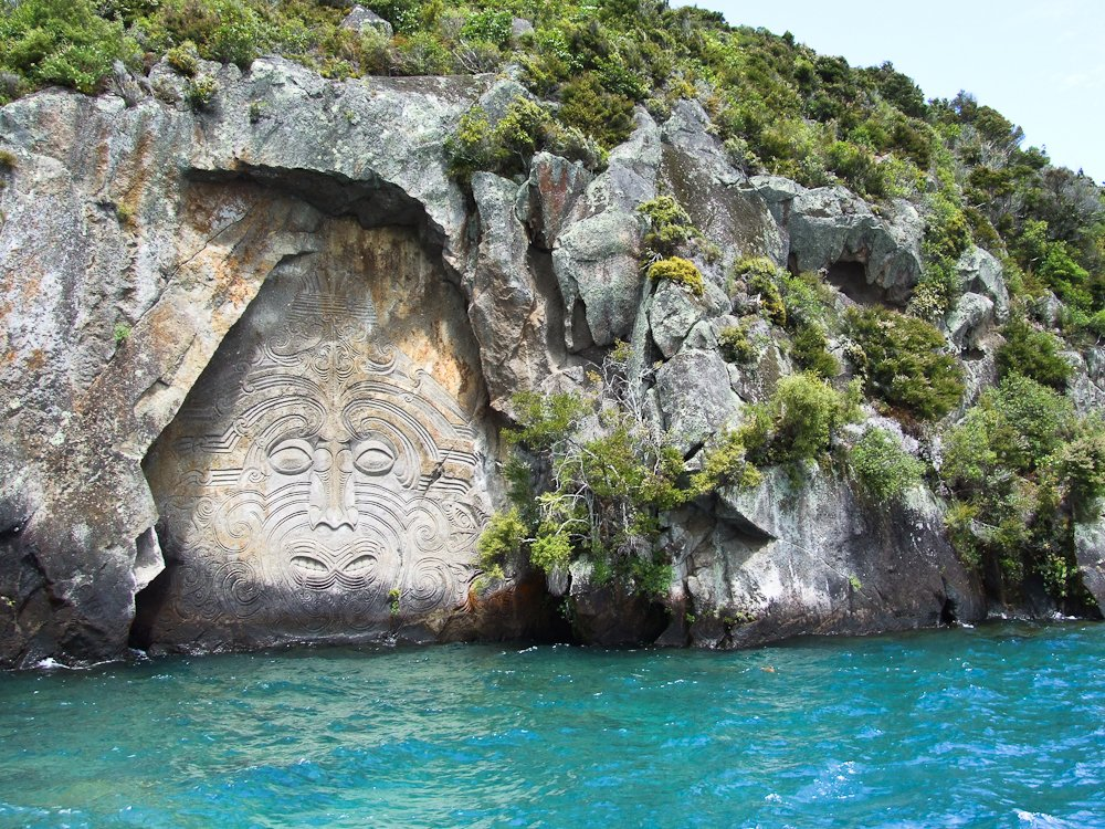 A spectacular Maori rock carving of Ngatoroirangi on the rock face in Mine Bay